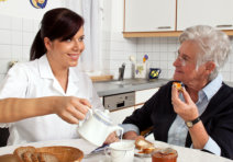 caregiver serving a meal to an old woman