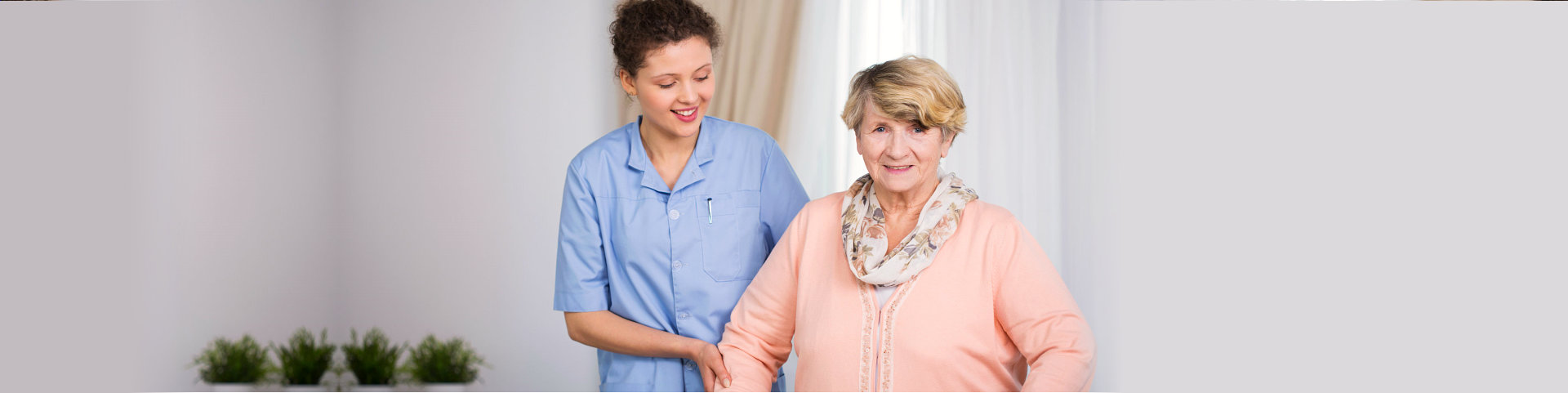caregiver assisting old woman in walking