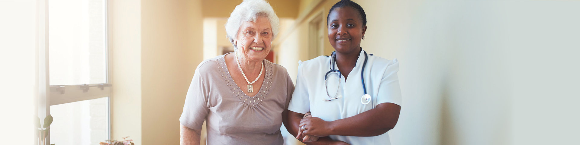caregiver and patient walking in the hallway
